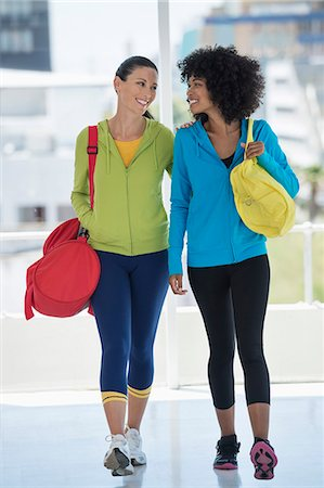 Two happy female friends carrying gym bags Stock Photo - Premium Royalty-Free, Code: 6108-06906944