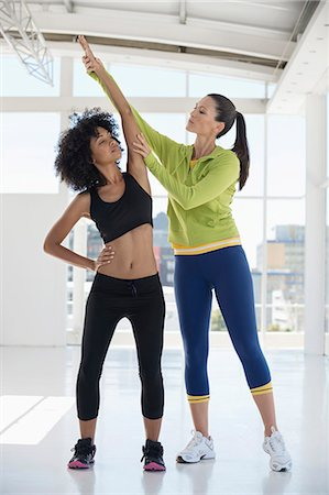Female instructor assisting a woman in a gym Stock Photo - Premium Royalty-Free, Code: 6108-06906991