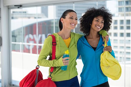 Two happy female friends carrying gym bags Stock Photo - Premium Royalty-Free, Code: 6108-06906992