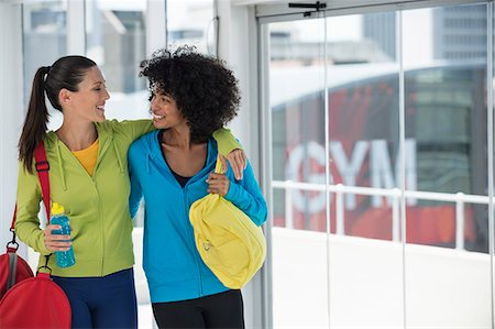 Two happy female friends carrying gym bags Stock Photo - Premium Royalty-Free, Code: 6108-06906912