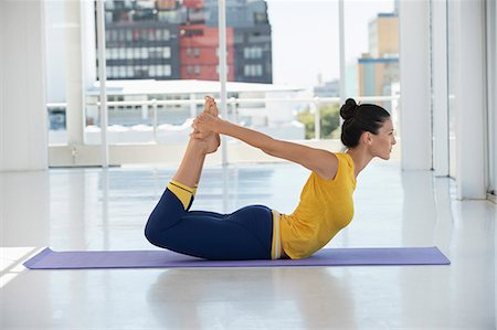 stretching (people exercising) - Woman exercising on exercise mat in a gym Stock Photo - Premium Royalty-Free, Code: 6108-06906926