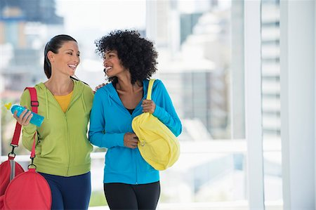 Two happy female friends carrying gym bags Stock Photo - Premium Royalty-Free, Code: 6108-06906934
