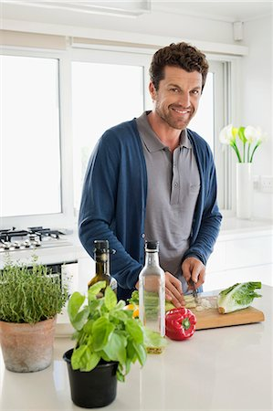 Man chopping vegetables in a kitchen Stock Photo - Premium Royalty-Free, Code: 6108-06907064
