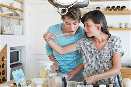 Woman tasting food to her husband in the kitchen Stock Photo - Premium Royalty-Free, Code: 6108-06907071