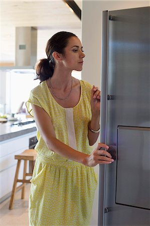 fridge - Woman opening a refrigerator in the kitchen Stock Photo - Premium Royalty-Free, Code: 6108-06907074