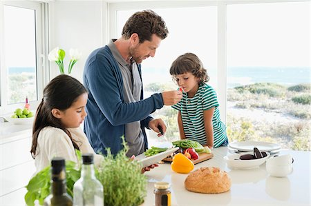 self indulgence - Man preparing food for his children Stock Photo - Premium Royalty-Free, Code: 6108-06907075
