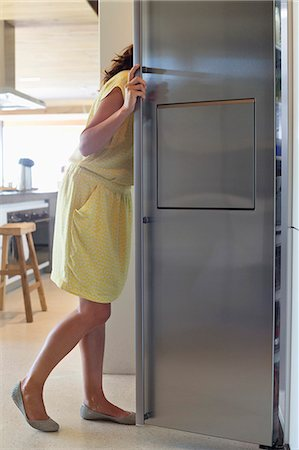 fridge - Woman looking into a refrigerator in the kitchen Stock Photo - Premium Royalty-Free, Code: 6108-06907094