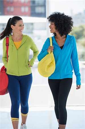 Two happy female friends carrying gym bags Stock Photo - Premium Royalty-Free, Code: 6108-06907008