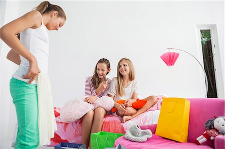 Girl trying on skirt with her friends at a slumber party Stock Photo - Premium Royalty-Free, Code: 6108-06907016