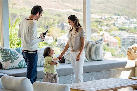 Couple standing in a living room with their daughter Stock Photo - Premium Royalty-Free, Code: 6108-06907147