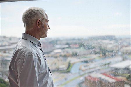 Man looking through a window Stock Photo - Premium Royalty-Free, Code: 6108-06907153