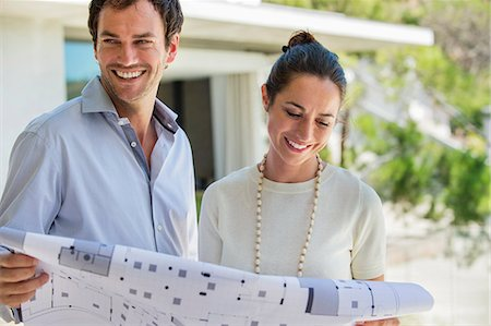 Couple holding a blueprint and smiling Stock Photo - Premium Royalty-Free, Code: 6108-06907179