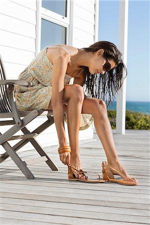 Beautiful woman putting on sandal at beach resort Stock Photo - Premium Royalty-Free, Code: 6108-06907261