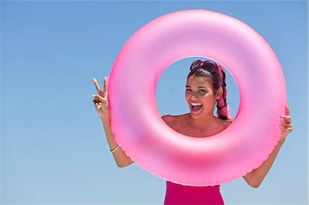 Beautiful woman looking through an inflatable ring on the beach Stock Photo - Premium Royalty-Free, Code: 6108-06907279