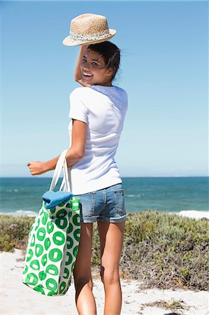 Happy woman carrying a bag on the beach Stock Photo - Premium Royalty-Free, Code: 6108-06907291