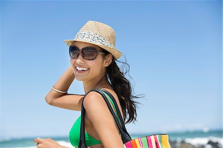 dark glasses - Beautiful woman smiling on the beach Stock Photo - Premium Royalty-Free, Code: 6108-06907292