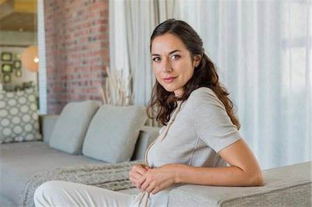 Portrait of a beautiful woman sitting on a couch Stock Photo - Premium Royalty-Free, Code: 6108-06907208