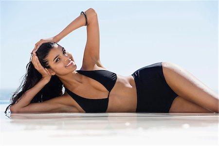 Beautiful woman in bikini lying on the beach Stock Photo - Premium Royalty-Free, Code: 6108-06907227