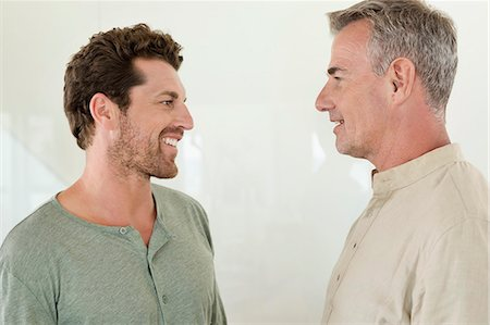 Father and son smiling at each other Stock Photo - Premium Royalty-Free, Code: 6108-06907313