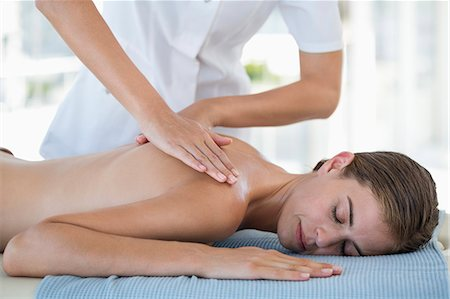 Woman receiving back massage from a massage therapist Stock Photo - Premium Royalty-Free, Code: 6108-06907473