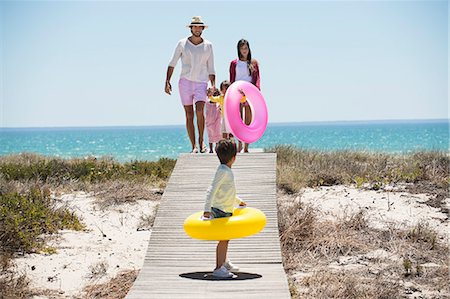 family  fun  outside - Children with their parents holding inflatable rings on a boardwalk on the beach Stock Photo - Premium Royalty-Free, Code: 6108-06907544