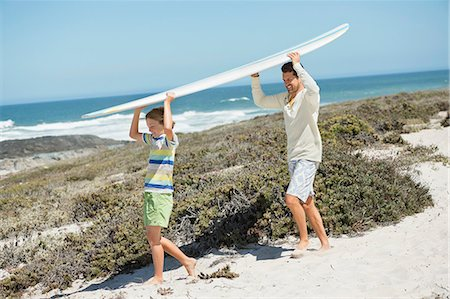 pre-teen beach - Man and his son carrying a surfboard on the beach Stock Photo - Premium Royalty-Free, Code: 6108-06907559