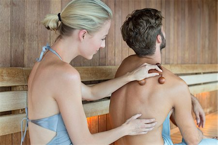 Woman massaging on her friend's back with a massager in a sauna Stock Photo - Premium Royalty-Free, Code: 6108-06907503