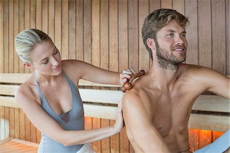 Woman massaging on her friend's back with a massager in a sauna Stock Photo - Premium Royalty-Free, Code: 6108-06907532