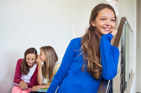 Close-up of a girl smiling with her friends whispering in the background Stock Photo - Premium Royalty-Free, Code: 6108-06907688