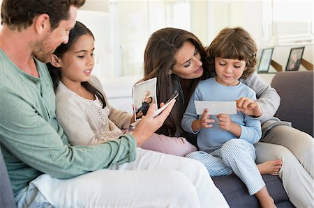 four - Parents showing photographs to their children Stock Photo - Premium Royalty-Free, Code: 6108-06907613
