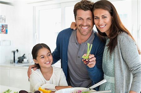 Couple with their daughter enjoying in the kitchen Stock Photo - Premium Royalty-Free, Code: 6108-06907627