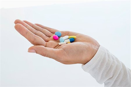 Close-up of a woman's hand holding medicines Stock Photo - Premium Royalty-Free, Code: 6108-06907759