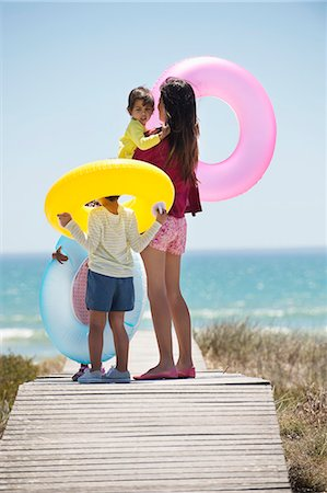 Woman with her children holding inflatable rings on a boardwalk on the beach Stock Photo - Premium Royalty-Free, Code: 6108-06907717