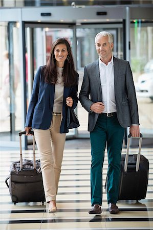 Business couple pulling suitcases in a hotel lobby Stock Photo - Premium Royalty-Free, Code: 6108-06907849