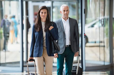 Business couple pulling suitcases in a hotel lobby Stock Photo - Premium Royalty-Free, Code: 6108-06907851