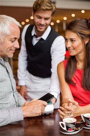 Waiter showing credit card reader to a couple on a table in a restaurant Stock Photo - Premium Royalty-Free, Code: 6108-06907863