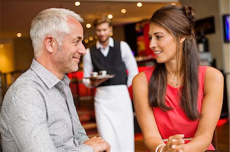 Couple smiling in a restaurant with waiter in the background Stock Photo - Premium Royalty-Free, Code: 6108-06907861