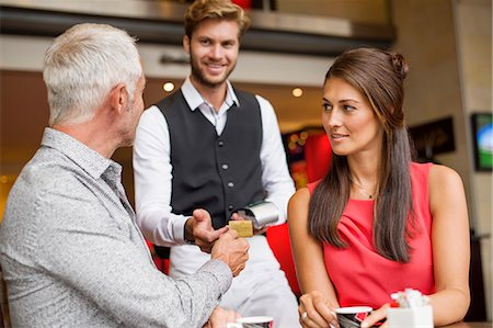 Couple paying with a credit card to a waiter in a restaurant Stock Photo - Premium Royalty-Free, Code: 6108-06907862