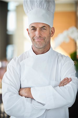 Portrait of a chef smiling with arms crossed Stock Photo - Premium Royalty-Free, Code: 6108-06907879