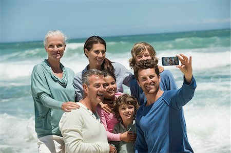 Happy multi-generation family taking a self portrait with a cell phone on the beach Stock Photo - Premium Royalty-Free, Code: 6108-06907891
