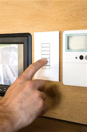 Person pressing switch of a security camera control panel Stock Photo - Premium Royalty-Free, Code: 6108-06907818