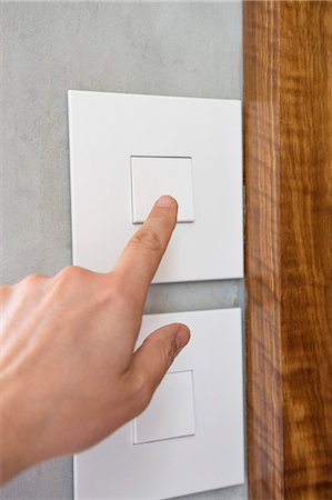 Close-up of a person's hand pressing a light switch Stock Photo - Premium Royalty-Free, Code: 6108-06907831