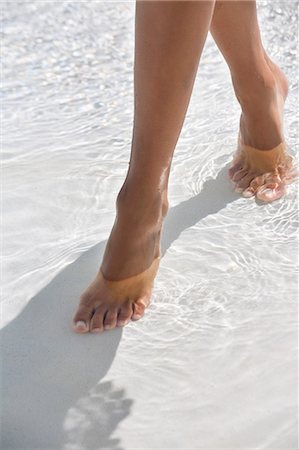 female feet close up - Woman walking in water on the beach Stock Photo - Premium Royalty-Free, Code: 6108-06907958