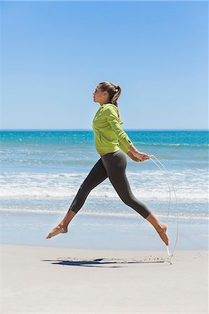 Woman jumping rope on the beach Stock Photo - Premium Royalty-Free, Code: 6108-06907989