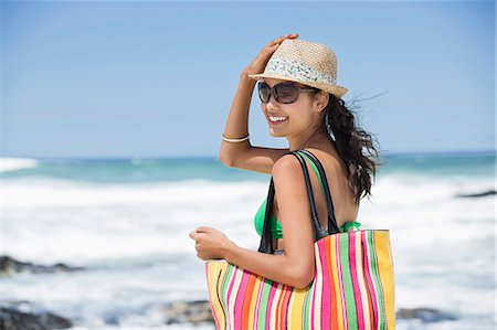 Beautiful woman smiling on the beach Stock Photo - Premium Royalty-Free, Code: 6108-06907923