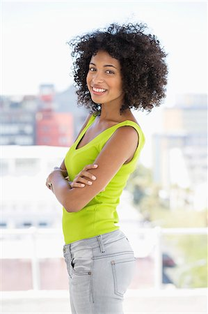 Woman standing with her arms crossed and smiling Stock Photo - Premium Royalty-Free, Code: 6108-06908056