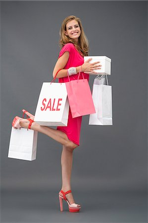 Portrait of a woman posing with shopping bags and smiling Stock Photo - Premium Royalty-Free, Code: 6108-06908060