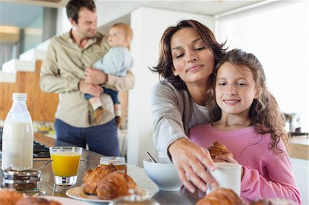 Girl having breakfast beside her mother at a kitchen counter Stock Photo - Premium Royalty-Free, Code: 6108-06908084