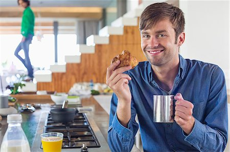 stove - Man having breakfast at a kitchen counter with his wife in the background Stock Photo - Premium Royalty-Free, Code: 6108-06908086