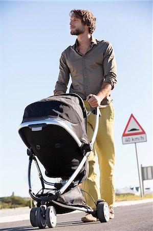 Man pushing a baby stroller Stock Photo - Premium Royalty-Free, Code: 6108-06908038